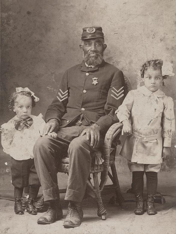 An unidentified black Union Army veteran, with two children, c. 1900