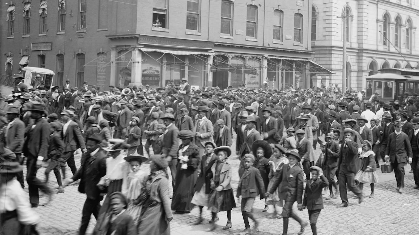 A crowd walks down the street celebrating Juneteenth