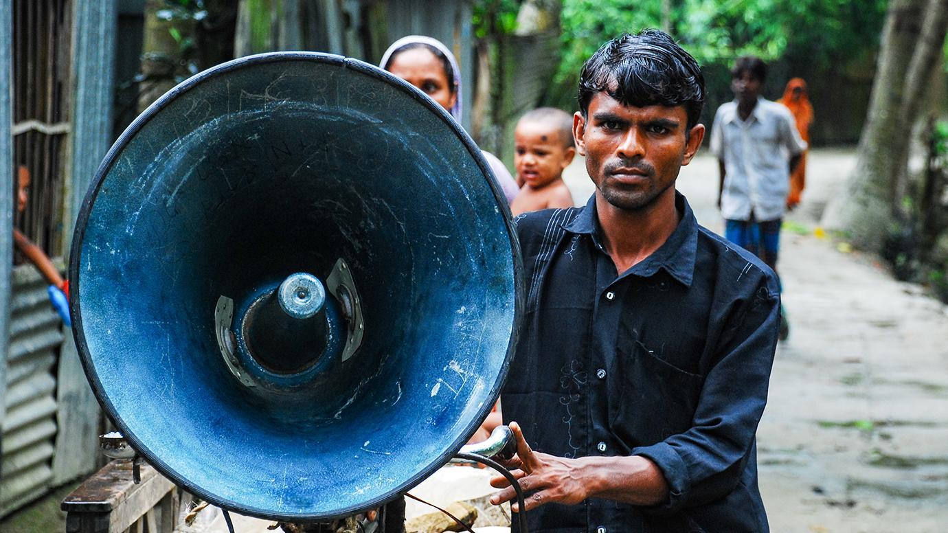 A man with a portable megaphone in rural Bangladesh