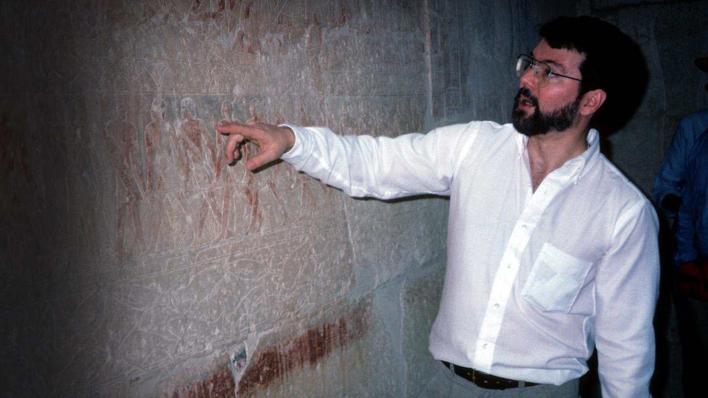 Robert Ritner gestures to markings inside a                      tomb
