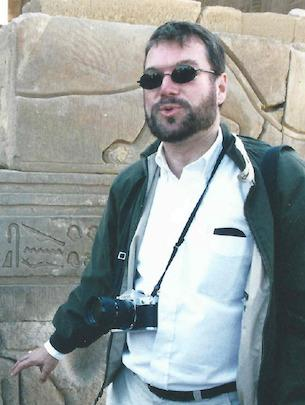 Robert Ritner wearing a green jacket and a                          camera hanging from his neck