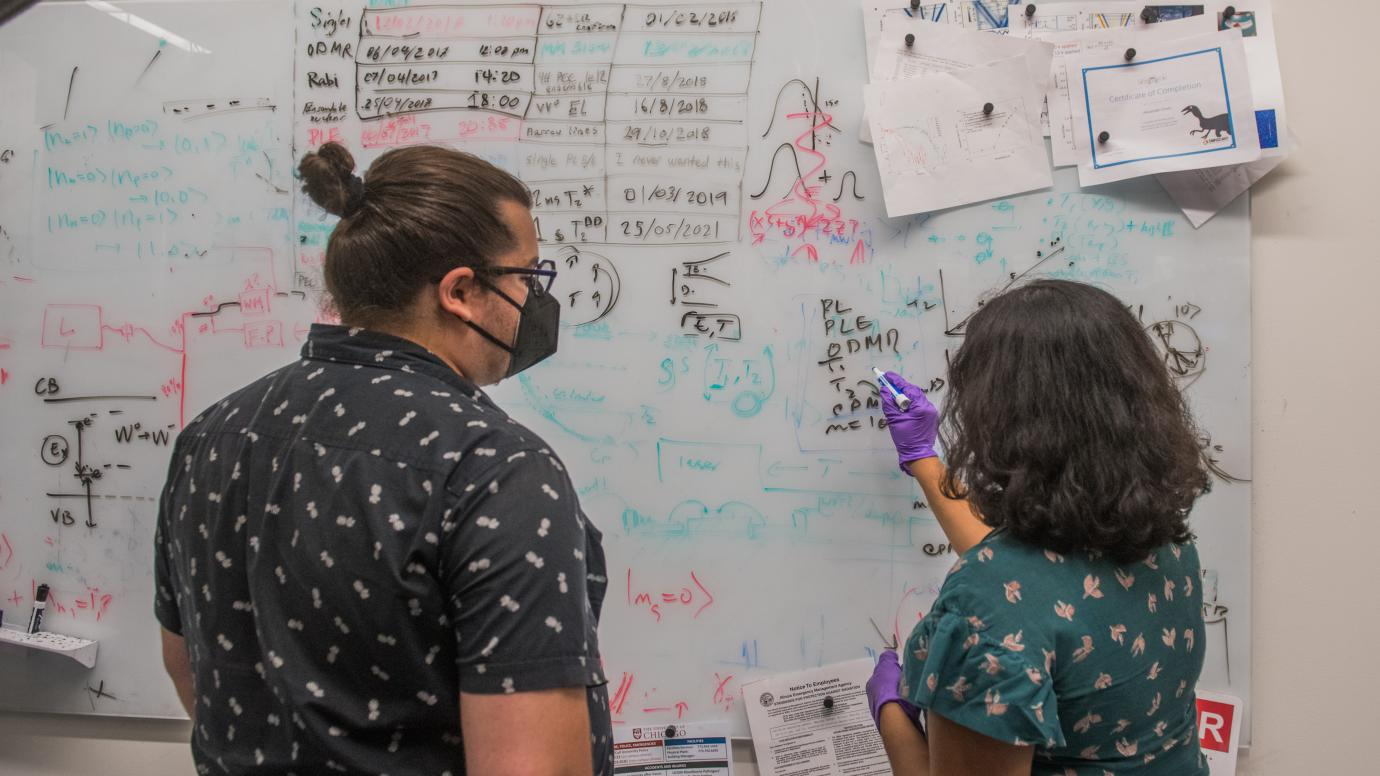 Two scientists at whiteboard with many equations
