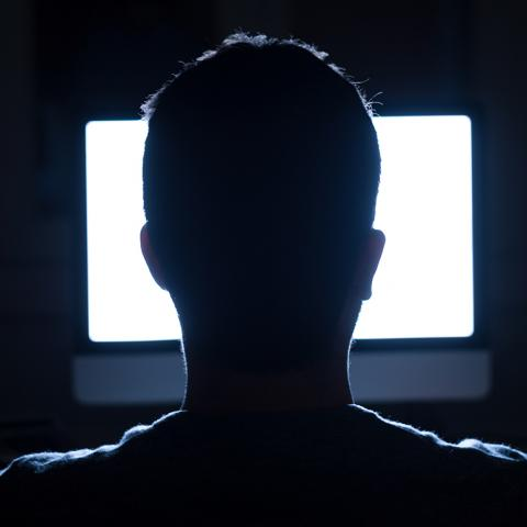 Man sitting at computer in dark room
