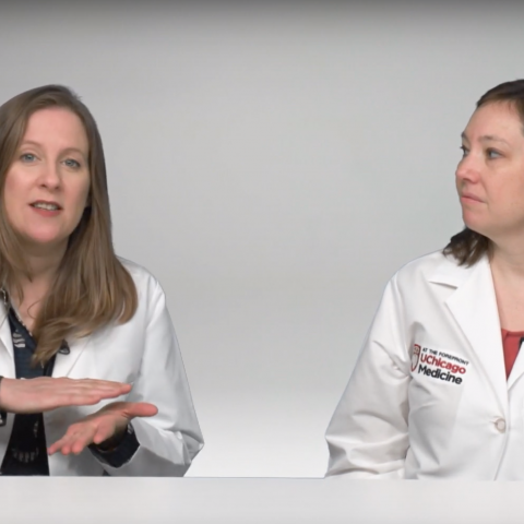 Two doctors in lab coats discuss coronavirus sitting at a table
