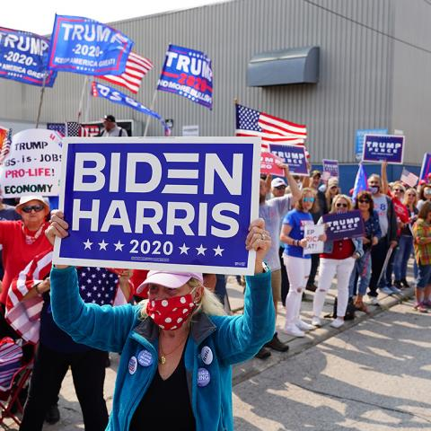 Woman holding a Biden sign in front of Trump supporters