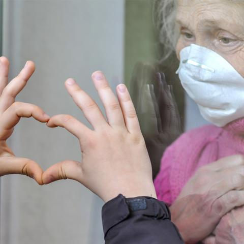 Man standing outside eldery woman's window with hands in the shape of a heart