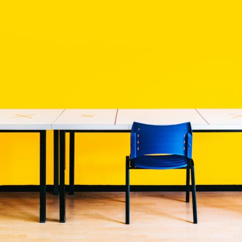 School classroom with yellow walls and blue chairs