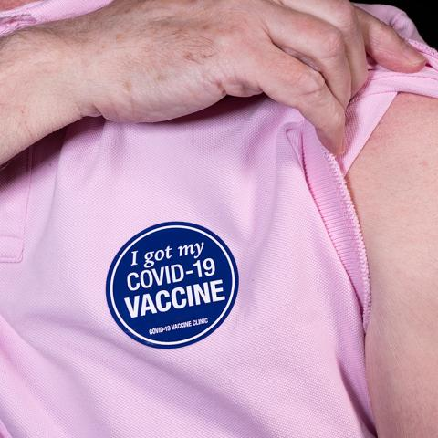 Person lifting the sleeve of their shirt to show the bandage over their covid-19 vaccination