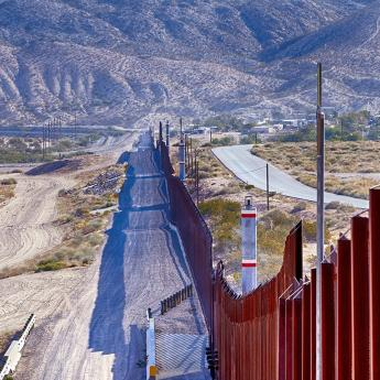 Photo of border wall with mountains in the background