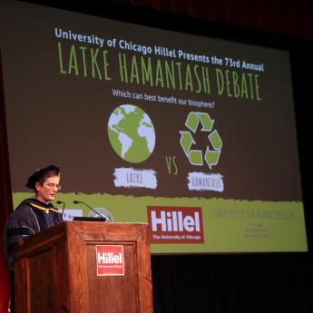 Scholar Ben Callard stands at a podium in front of a screen announcing the 2019 Latke Hamantash Debate at the University of Chicago