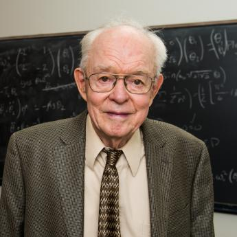 Prof. Parker in front of blackboard with equations