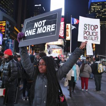 A protestor holds up signs during a demonstration against police brutality in New York City's Times Square.