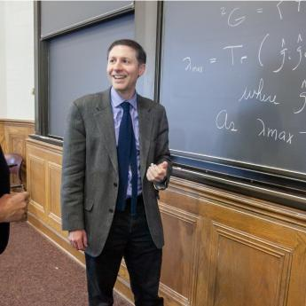 Three chemists discuss equations at blackboard