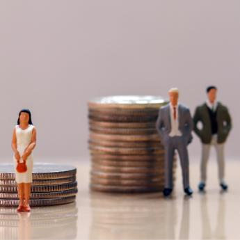 Toy figurines and coins, a wage gap symbol