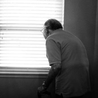 Elderly man standing with cane looking out window