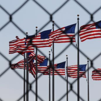 U.S. flags behind wire fence