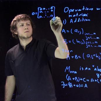 Asst. Prof. Daniil Rudenko writing equations on light board