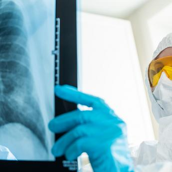 Medical worker in full protective gear examines a chest X-ray