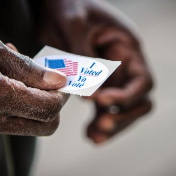 "Black voter holding an ""I voted"" sticker"