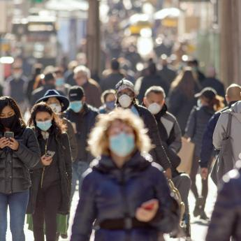 A street crowded with people wearing protective masks.