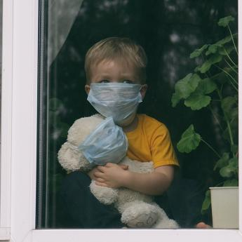 Child looking out window while hugging a stuffed animal