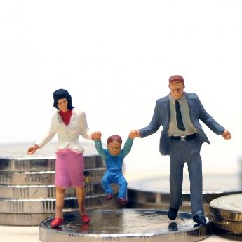 Two miniature figures lift their child up while standing on a pile of coins