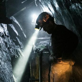 A coal miner with a headlamp works in a dark shaft