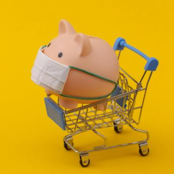 A piggy bank with a mask inside a toy shopping cart