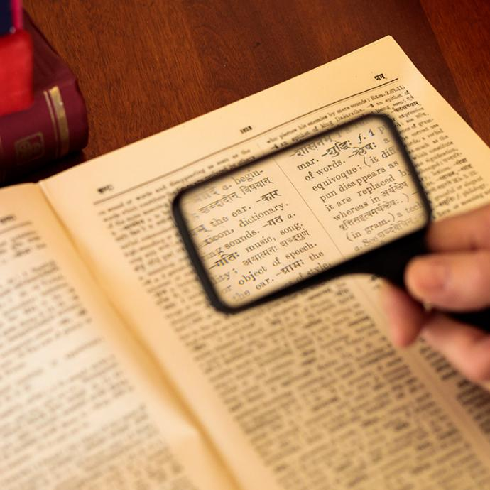 Magnifying glass looking at dictionary