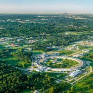 Aerial image of the Advanced Photon Source, a large circular building, with the Chicago skyline in the distance
