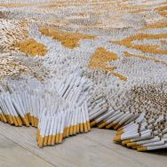"A detailed shot of Xu Bing's ""1st Class,"" which uses cigarettes to mimic a tiger-skin rug."