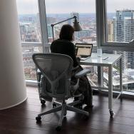 Sarah Cobey working at her desk in a high-rise apartment overlooking Chicago, with dog curled up in a bed next to her