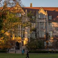 People walk past Eckhart Hall on the campus of the University of Chicago with trees turning colors.