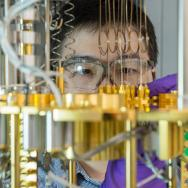 Scientist Dafei Jin working with gloves and goggles on an array of brass tubes