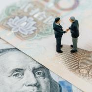 Toy men shake hands, standing on cash bills from the United States and China